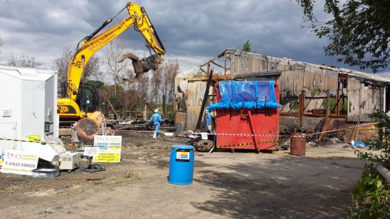 Fired asbestos contaminated barns. Total segregation and decontamination in accordance with asbestos regs 2012 and ASB1 remote demolition.: Swipe To View More Images